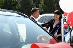 Токио Олимпиадасында күрөш боюнча коло медаль уткан Мээрим Жуманазарова жана президент Садыр Жапаров белекке берилген унаанын алдында