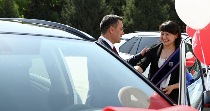 Президент Садыр Жапаров дарит автомобиль марки Toyota Rav 4 бронзовой медалистке Олимпийских игр в Токио Мээрим Жуманазаровой на торжественной церемонии вручения Токио в госрезиденции Ала-Арча.