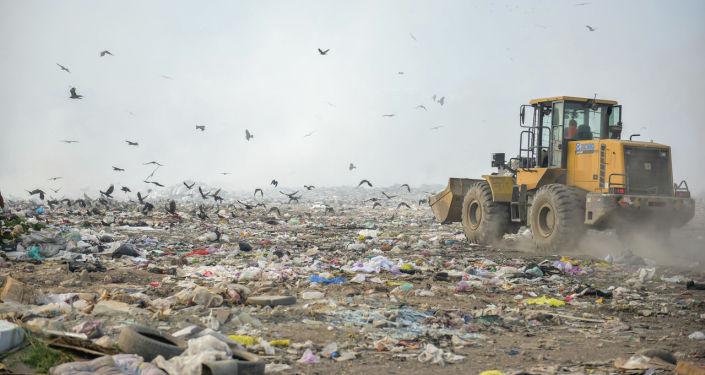 Грейдер на свалке во время подписания меморандума о проектировании и строительстве мусороперерабатывающего завода в Бишкеке. 23 августа 2021 года