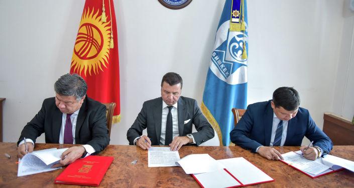И. о. мэра Айбек Джунушалиев, министр инвестиций Алмамбет Шыкмаматов и президент Biotrend Energy Илхан Доган во время подписания меморандума о строительстве мусороперерабатывающего завода в Бишкеке. 23 августа 2021 года
