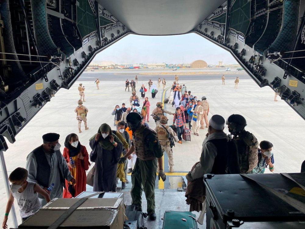 Испания жарандары менен афганистандыктар Кабулдагы аэропорттон коопсуз жайга учуп чыгуу үчүн аскердик аба кемесине түшүп жатышат