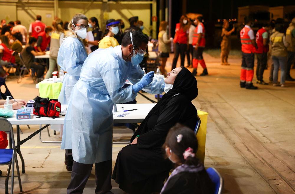 Качкындар Кабулдан учуп келгенден кийин Испаниянын Торрехон шаарындагы аба базасында COVID-19га тест тапшырып жатат