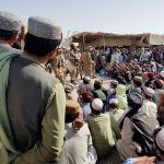 Пакистандык армиянын аскерлери көзөмөл-өткөрүү жайынын жанында топтолгон эл менен сүйлөшүп жатышат