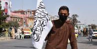 Талибан кыймылынын тарапташы желегин кармап бара жатат. Архивдик сүрөт