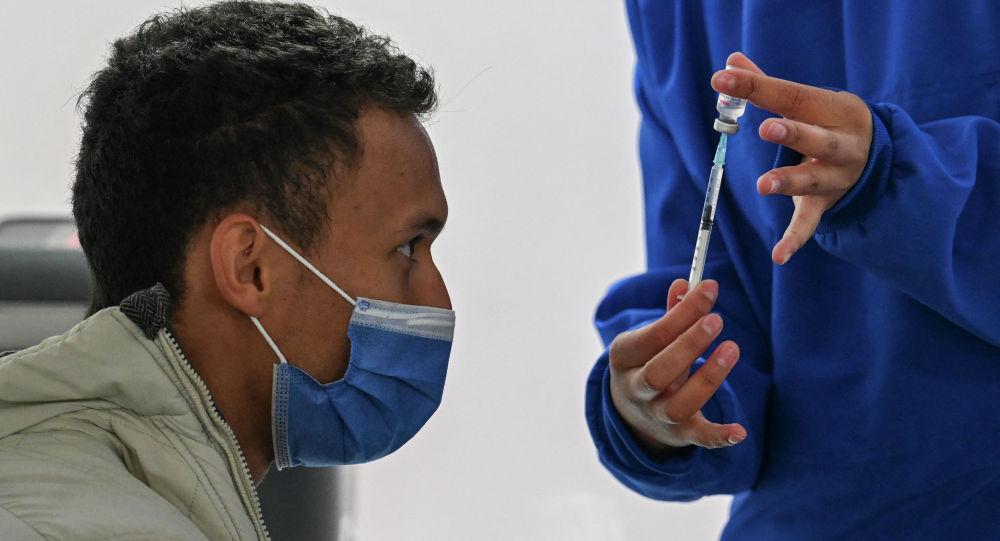 Медик показывает мужчине вакцину против COVID-19. Архивное фото