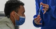 Медицинский работник показывает мужчине ампулу с вакциной против COVID-19. Архивное фото