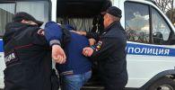 Россия полиция кызматкерлери коомдук тартипти бузган кишини кармоодо. Архивдик сүрөт
