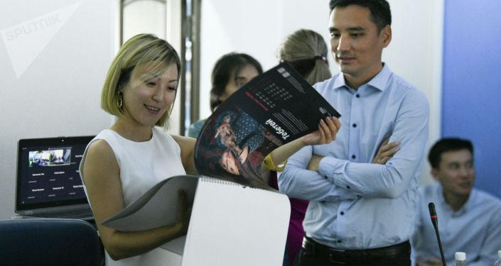 Участники во время просмотра календаря Sputnik на конференции на тему развития предпринимательства в Кыргызстане. 26 августа 2021 года