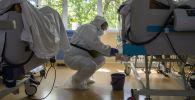Ооруканада коронавируска кабылган бейтаптарды караган медик. Архивдик сүрөт