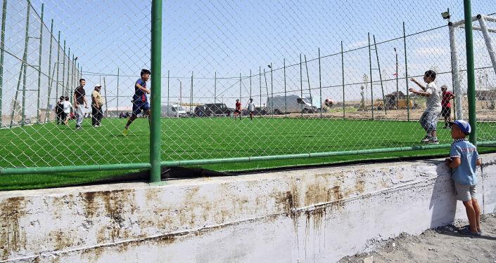 Футоблисты местной молодежной команды в футбольном поле восстановленной школы в селе Максат Лейлекского района