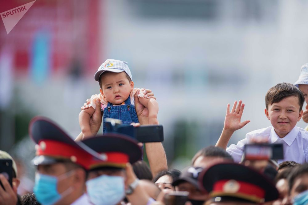 Родители поднимают детей, чтобы те смогли увидеть проезжающую мимо военную технику