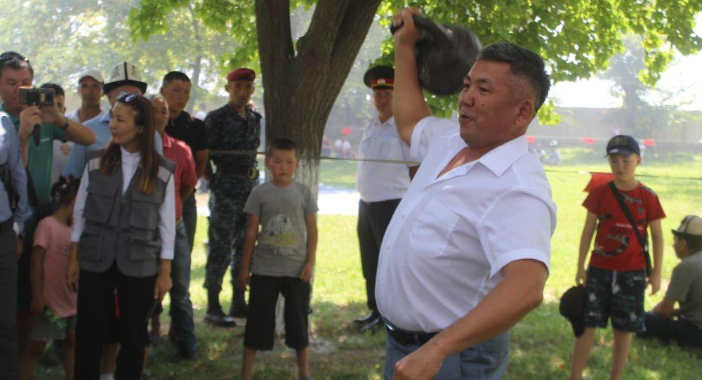 Полномочный представитель президента в Баткенской области Абдикарим Алимбаев поднимает гирю во время праздничных гуляний в честь Дня независимости Кыргызстана
