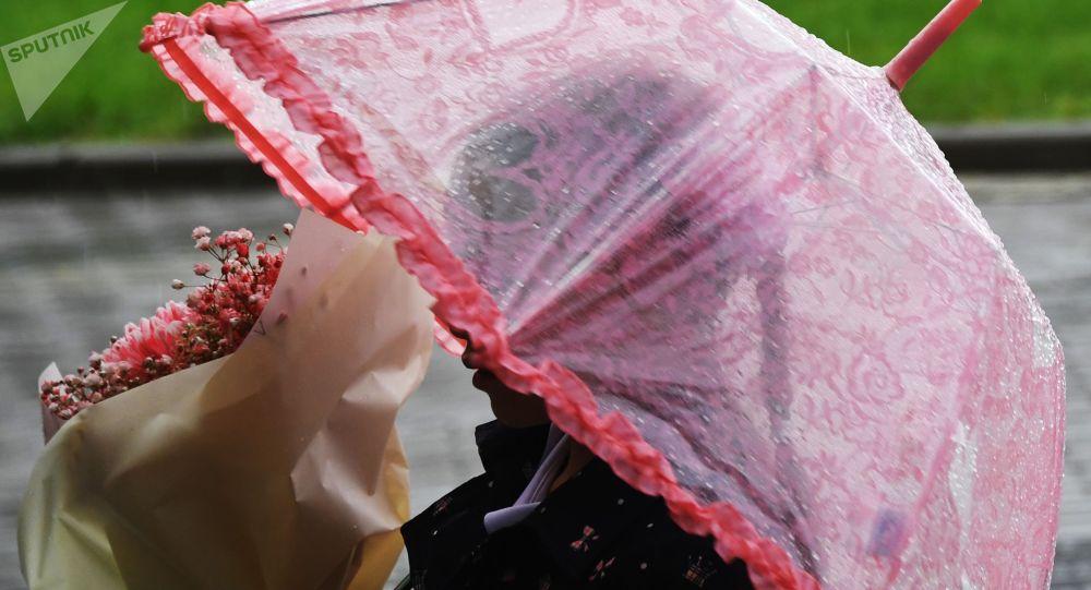 Школьница с зонтом во время дождя