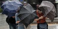 Люди с зонтами во время сильного ветра и дождя. Архивное фото