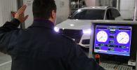 Технический эксперт проводит осмотр автомобиля. Архивное фото