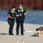 Полиция кызматкерлери жээкте эс алып жаткан кыз менен сүйлөшүп жатышат (Мельбурн)