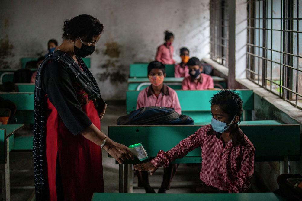 Индиянын Нью-Дели шаарынын четиндеги Ноид аймагында жарым-жартылай ачылган мектептин мугалими окуучулардын дене табын текшерип жатат