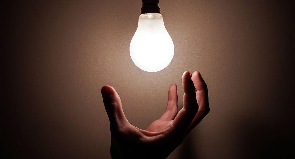 Рука тянется к горящей в комнате лампочке. Иллюстративное фото