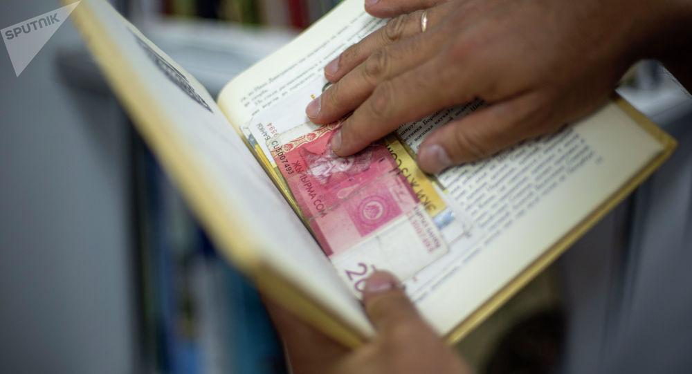 Мужчина прячет заначку в книгу. Иллюстративное фото