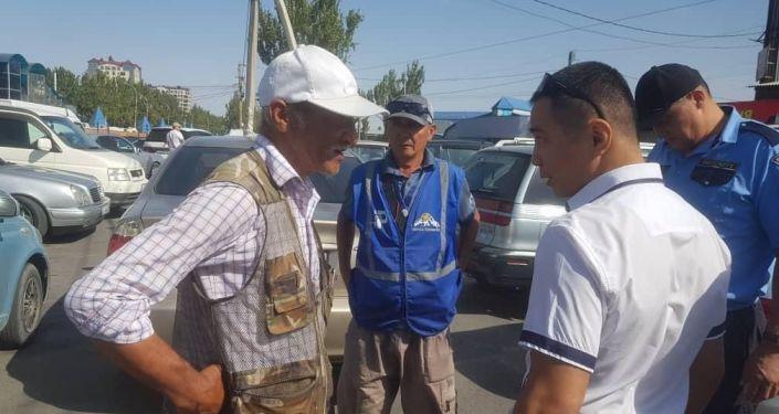Задержанные, незаконно работавшие парковщики, около рынка Мадина в Бишкеке. 09 сентября 2021 года