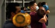 Люди в масках во время занятий в тренажерном зале. Архивное фото