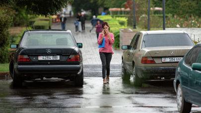 Девушка разговаривает по телефону во время дождя в Бишкеке. Архивное фото