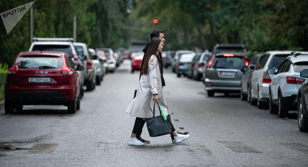 Пешеходы переходят дорогу во время кратковременного дождя в Бишкеке