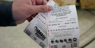 Мужчина держит свои лотерейные билеты Mega Millions и Powerball. Архивное фото