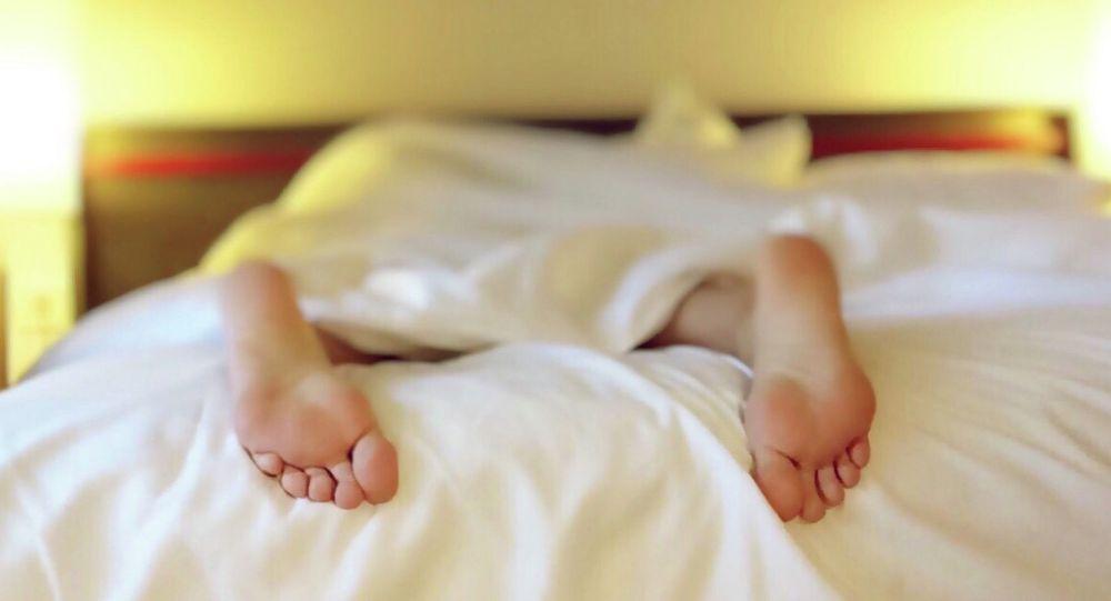 Человек спит на кровати. Иллюстративное фото