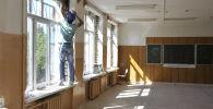 Мектеп кабинетине ремонт жасап жаткан жумушчу. Архив