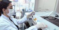 Сотрудница лаборатории держит пробирки для проведения ПЦР-тестов на коронавирус . Архивное фото