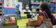 Фармацевт приветствует клиента в аптеке в Франции. Архивное фото