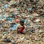 Сын сборщика мусора отдыхает, пока его отец ищет предметы, которые можно перепродать, на свалке в Алу-Лием в Лхоксеумаве (Индонезия). 15 сентября 2021 года