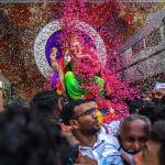 Паломники бросают лепестки цветов в бога Ганеши, во время традиционного осеннего фестиваля Ганеш Чатуртхи в Мумбаи (Индия). 19 сентября 2021 года