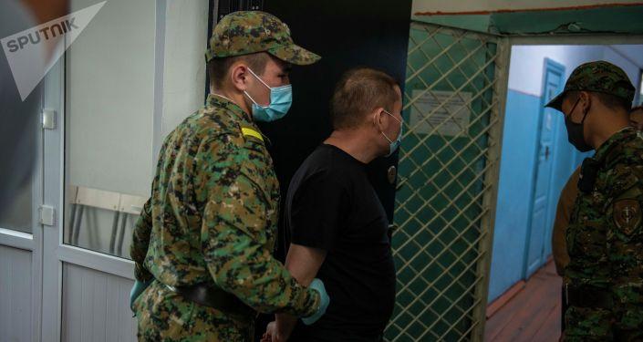 Сотрудники Департамента охраны исправительных учреждений и конвоирования ГСИН ведут задержанного