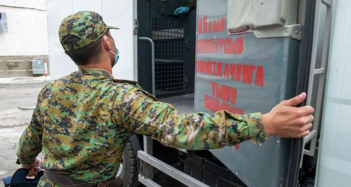 Сотрудник Департамента охраны исправительных учреждений и конвоирования ГСИН у служебного авто