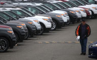 Мужчина идет мимо выставленных на продажу автомобилей. Архивное фото