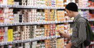 Покупатель в отделе молочной продукции гипермаркета. Архивное фото