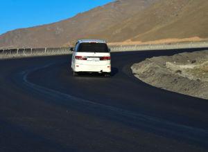 Автомобиль едет на новом асфальтобетонном покрытии на участке автодороги Бишкек-Ош (южная сторона перевала Тоо-Ашуу)