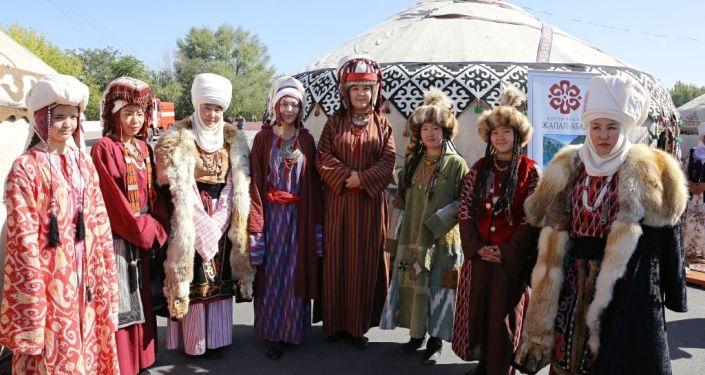 Люди в национальной одежде на туристической выставка-ярмарке в городе Ош