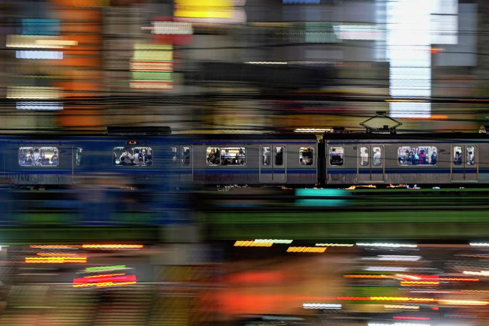 Люди в защитных масках в поезде, проезжающем через район Синдзюку в Токио. 22 сентября 2021 года