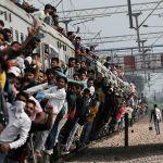 Люди цепляются за переполненный поезд в Индии.