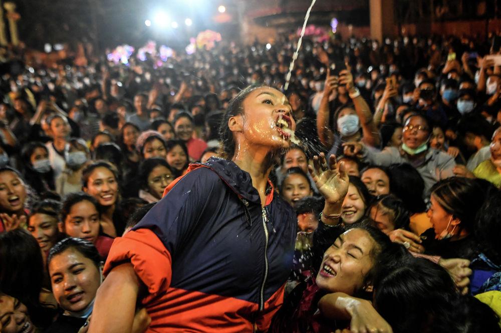 Верующие пьют вино из статуи Швет Бхайрава (бога защиты) во время фестиваля Индра Джатра в Катманду. 21 сентября 2021 года