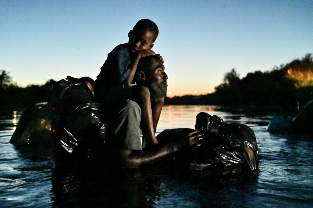 Гаитянский мигрант несет ребенка на плечах, когда пересекают реку Рио-Гранде между Мексикой и штатом Техас (США)