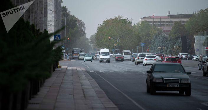 Автомобили на площади Ала-Тоо во время сильного ветра, который поднял в воздух пыль и песок в Бишкеке. 27 сентября 2021 года
