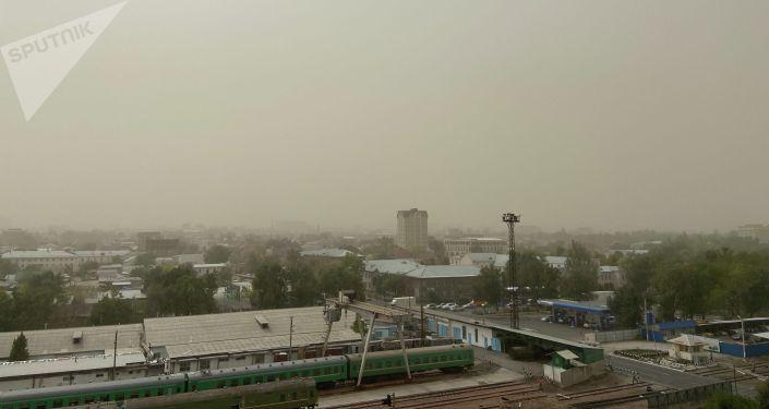 Вид на небо в Бишкеке во время сильного ветра, который поднял в воздух пыль и песок. 27 сентября 2021 года
