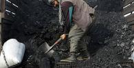 Продавец разгружает уголь. Архивное фото