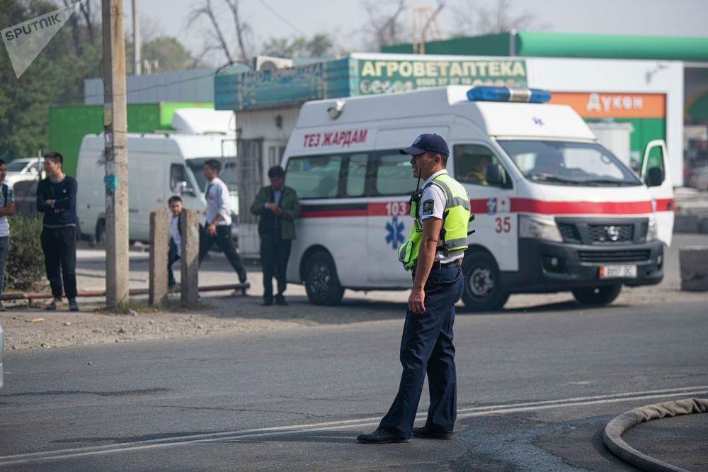 Сотрудник милиции и скорая помощь на месте пожара рядом с кафе Империя пиццы на улице Кулиева в Бишкеке