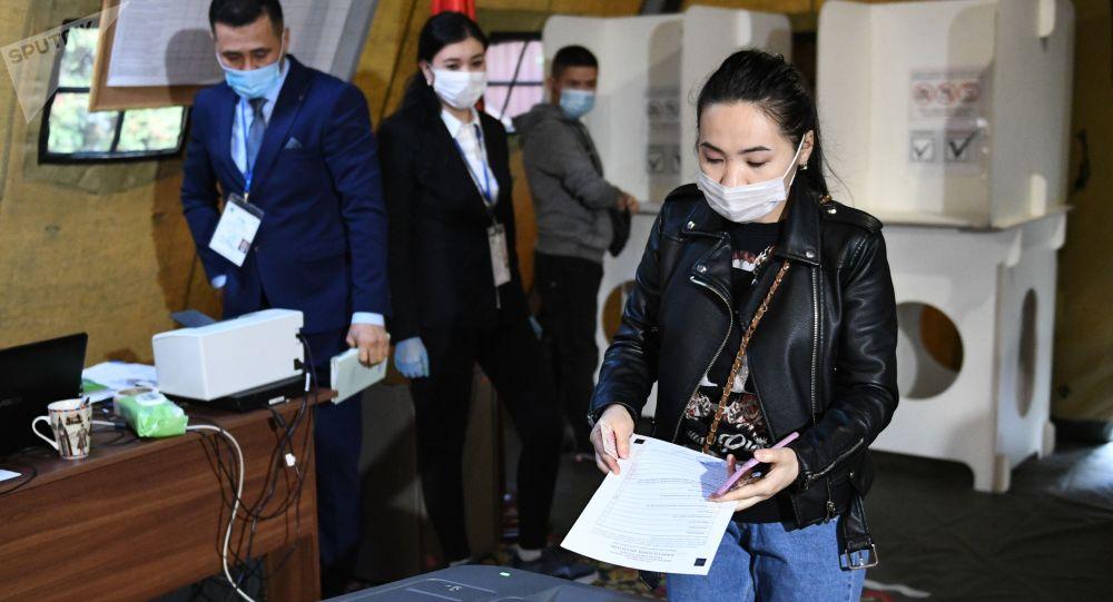 Девушка опускает бюллетень в урну для голосования. Архивное фото