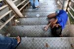 Мальчик лежит на лестнице пешеходного моста, прося милостыню. Архивное фото